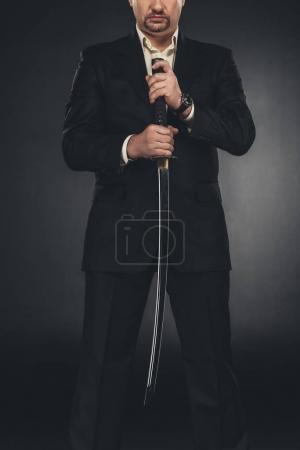 cropped shot of yakuza member in suit holding katana sword on black