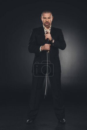 Photo pour Membre d'yakuza grave en costume tenant épée katana sur fond noir - image libre de droit