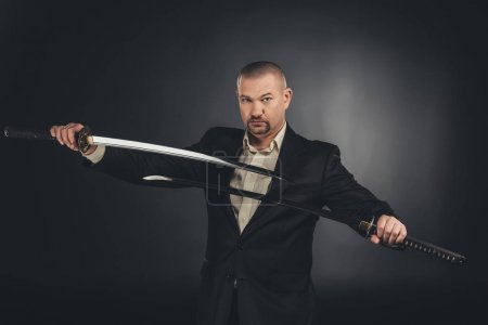 serious man in costume with dual katana swords on black