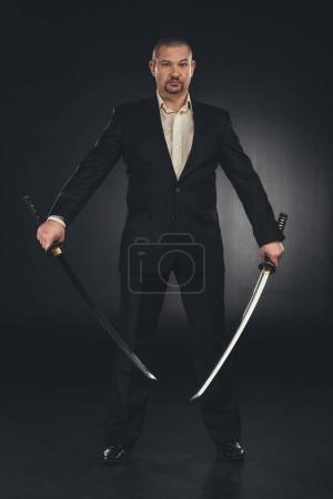 man in costume with dual katana swords on black