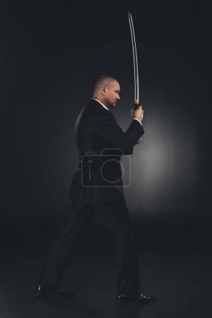 side view of yakuza member in suit with katana sword on black