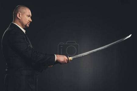 side view of man in suit with katana sword isolated on black
