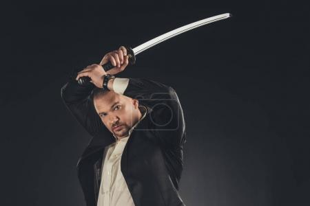 mature yakuza member in suit with katana sword isolated on black