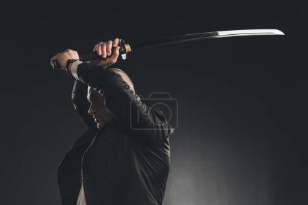side view of man in suit making hit with katana sword isolated on black
