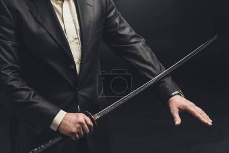 cropped shot of yakuza member cutting his arm for self punishment isolated on black