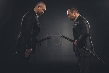 side view of modern samurai in suits bowing to each other isolated on black