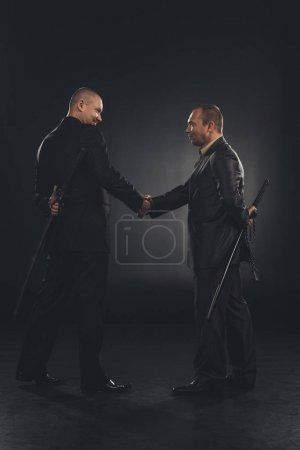 Photo for Side view of yakuza members shaking hands with katanas behind back isolated on black - Royalty Free Image