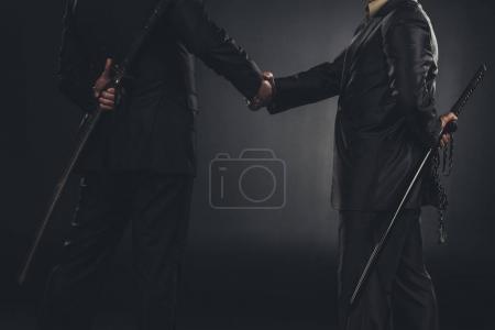 Photo for Cropped shot of yakuza members shaking hands with katanas behind back isolated on black - Royalty Free Image