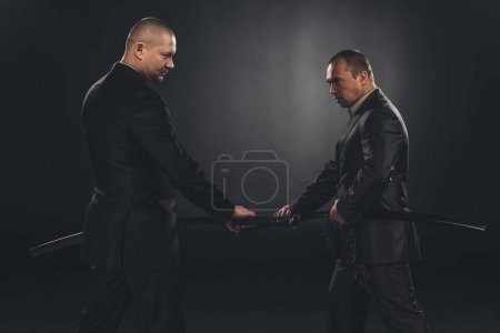 Photo for Side view of businessmen taking out katana swords for fight isolated on black - Royalty Free Image