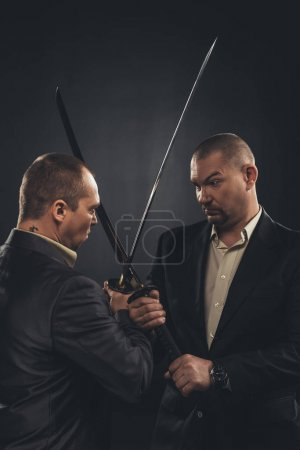Photo for Businessmen fighting with katana swords isolated on black - Royalty Free Image