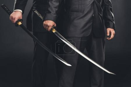 cropped shot of modern samurai with katana swords isolated on black