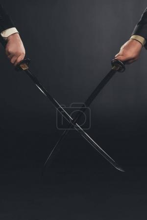 cropped shot of businessmen fighting with katana swords isolated on black