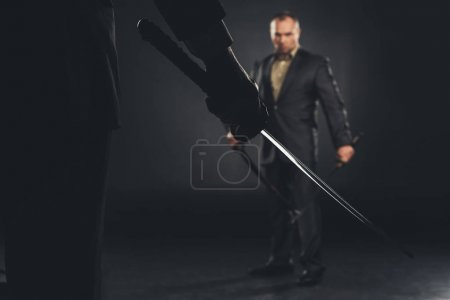 handsome modern samurai in suit ready to fight on black