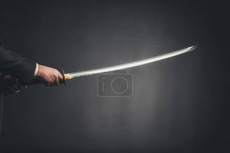 cropped shot of man holding katana on black