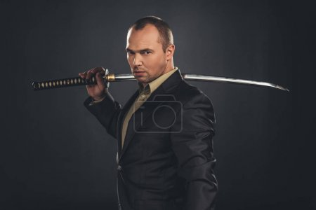 serious man in suit with katana sword isolated on black