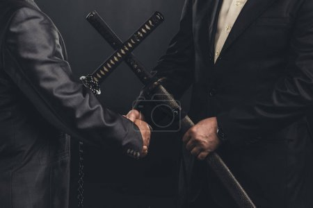 Photo for Cropped shot of meeting of yakuza members in suits with katana swords isolated on black - Royalty Free Image