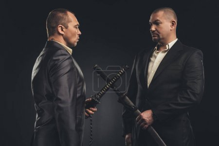 Photo for Meeting of modern samurai in suits with katana swords isolated on black - Royalty Free Image