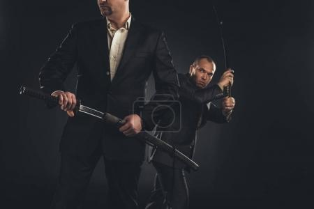 Photo for Two mature modern samurai with katanas isolated on black - Royalty Free Image
