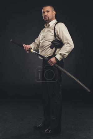 Photo pour Vue latérale du membre yakuza qui prend son épée katana - image libre de droit