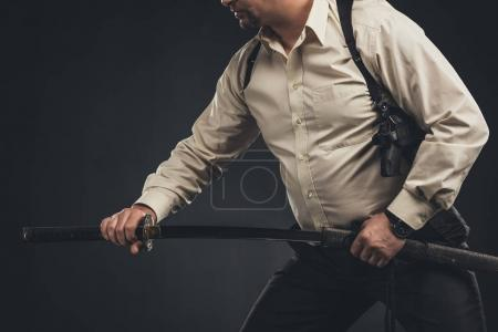 cropped shot of yakuza member taking out his katana sword