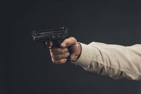 cropped shot of man holding gun isolated on black