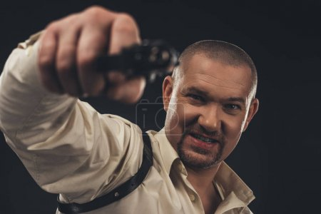 dangerous angry man aiming gun at camera isolated on black
