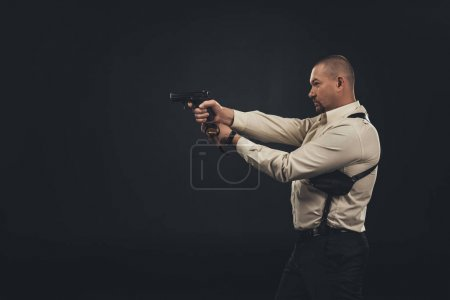 side view of killer holding gun isolated on black