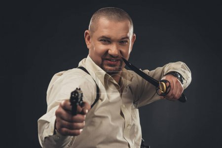 dangerous smiling man with knife and gun looking at camera