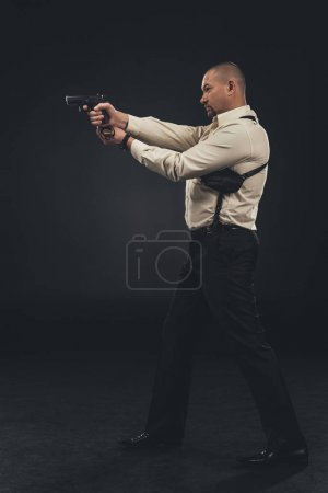 side view of security man holding gun on black