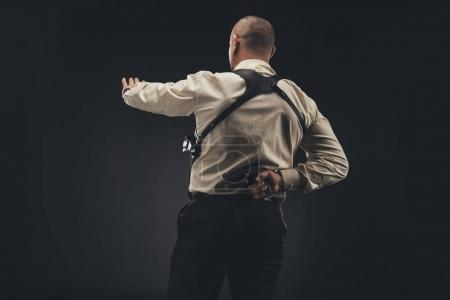 security man showing stop sign and holding gun behind back