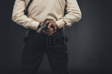 back view of man in shirt holding gun behind back