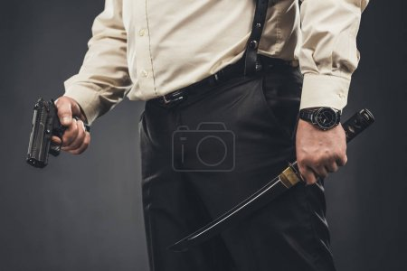 cropped shot of yakuza member with tanto knife and gun