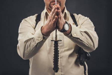 cropped shot of yakuza member holding blade of tanto knife