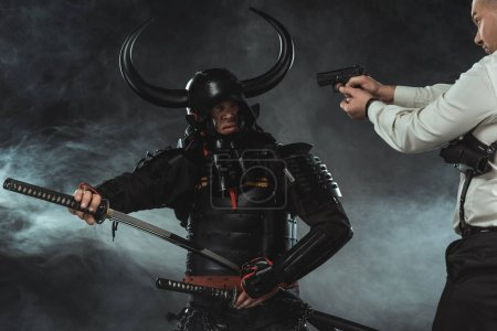 modern man aiming on samurai with gun while he taking out his sword