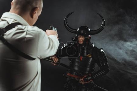 man aiming on armored samurai with gun
