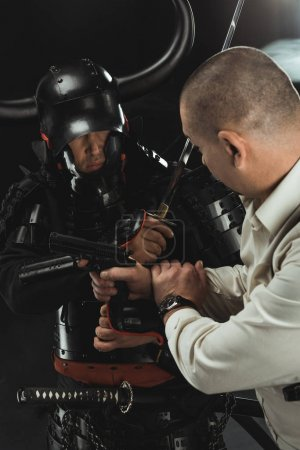 Photo pour Gros plan d'armure samouraï se battre avec l'homme qui tient fusil - image libre de droit