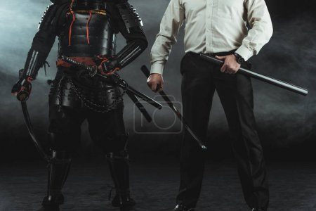cropped shot of modern man and samurai with katana swords on black