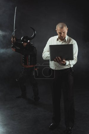 concentrated man using laptop while samurai standing behind him with sword