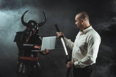 Photo pour Homme avec Katana debout dans fornt de samouraï alors qu'il utilise un ordinateur portable - image libre de droit