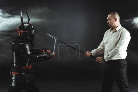 side view of man with katana standing in fornt of samurai while he using laptop