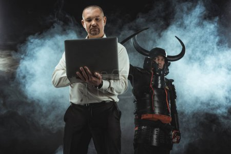 man using laptop while samurai standing behind him with sword