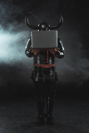 armored samurai holding laptop on dark background with smoke