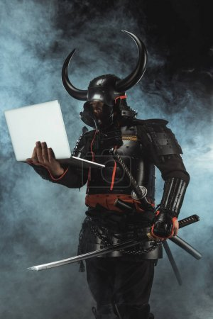 samurai in traditional armor holding laptop on dark background with smoke