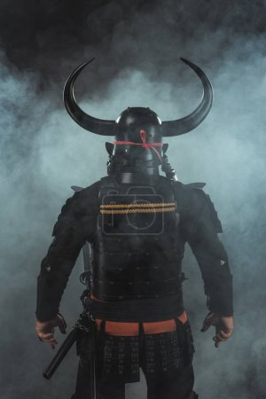 back view of samurai in traditional armor and horned helmet on dark background with smoke