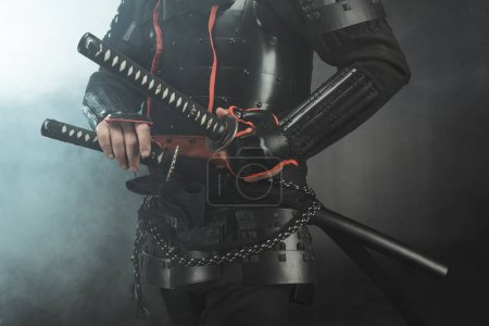 cropped shot of samurai in armor with swords on dark background with smoke