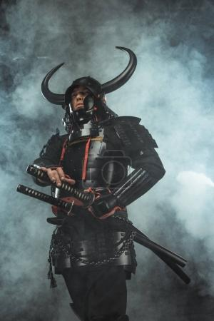 bottom view of samurai in japanese armor with swords on dark background with smoke