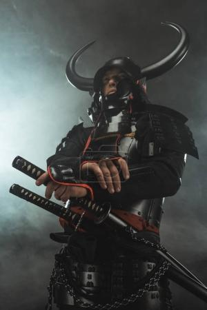 bottom view of samurai in traditional armor with swords on dark background with smoke