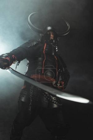 Photo pour Vue de dessous du samouraï en armure traditionnelle avec l'épée sur un fond sombre avec de la fumée - image libre de droit