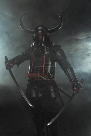 samurai in traditional armor with dual katana swords on dark background with smoke