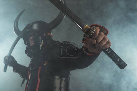 close-up shot of samurai in armor with dual katana swords on dark background with smoke